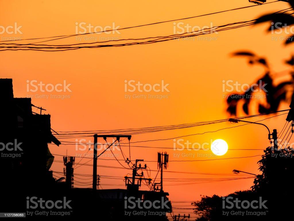Sonnenuntergang am Himmel hinter elektrischen Pole Silhouette und Gebäude. – Foto