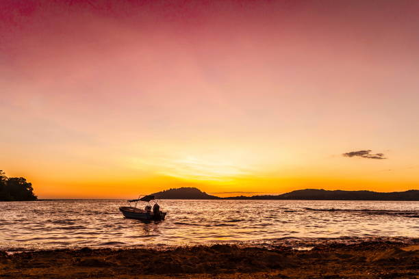 sunset on the beach in nosy be island with ship - italiansight foto e immagini stock