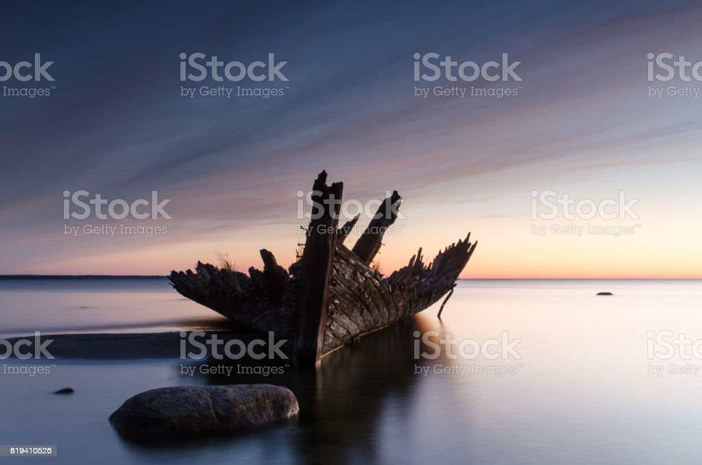 Sunset on the beach with an old sailboat wreck. stock photo