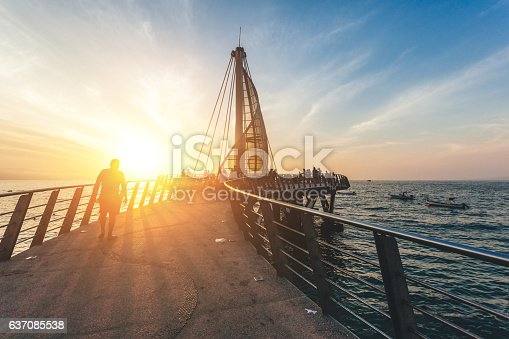 People walking and relaxing on the bridge as the sun goes down for the day.