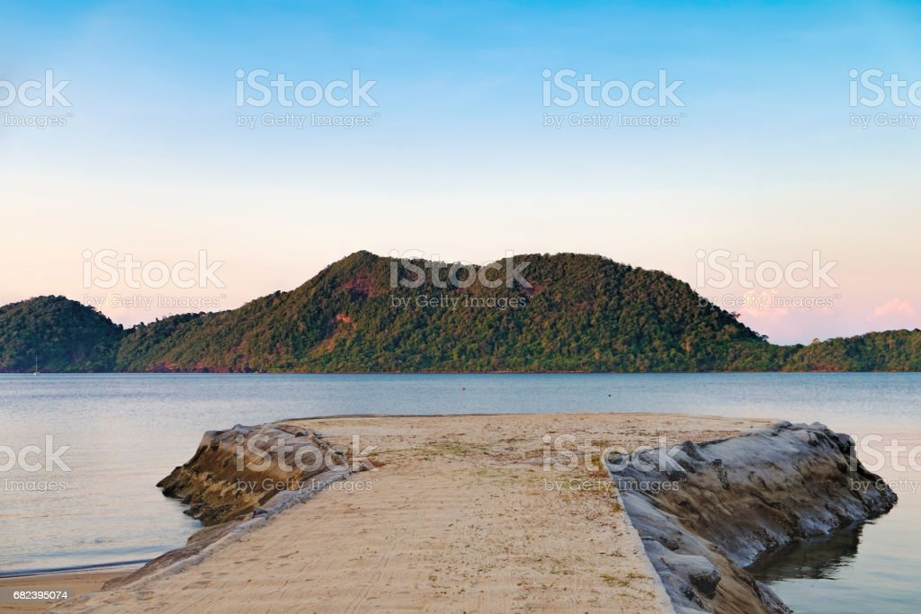 Sunset on the calm Thai beach with pier for boats royalty-free stock photo