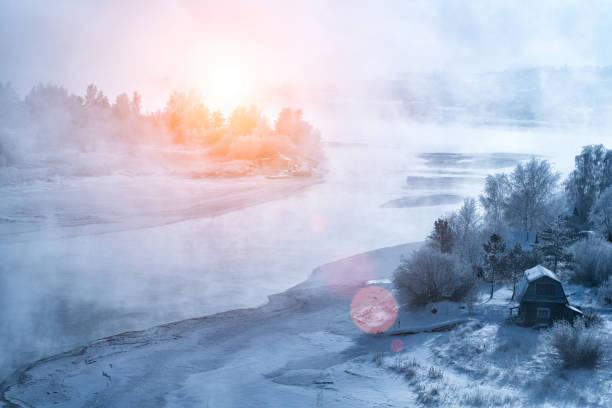 sunset on the frozen river - сибирь стоковые фото и изображения