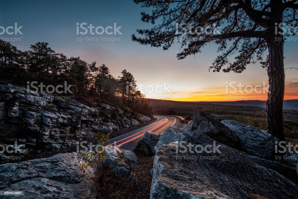 sunset on the highway and car lights in the Minnewaska State Park Preserve stock photo