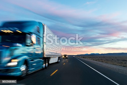 Stock photo from a driver of a vehicles point of view at sunset on a highway with passing cars and trucks.