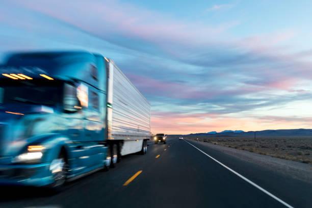sonnenuntergang auf der langstrecke autobahn - schweres nutzfahrzeug stock-fotos und bilder