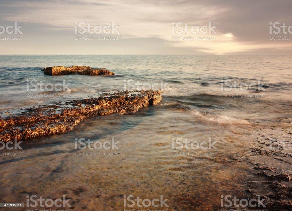 Sunset on the Mediterranean rocky beach royalty-free stock photo