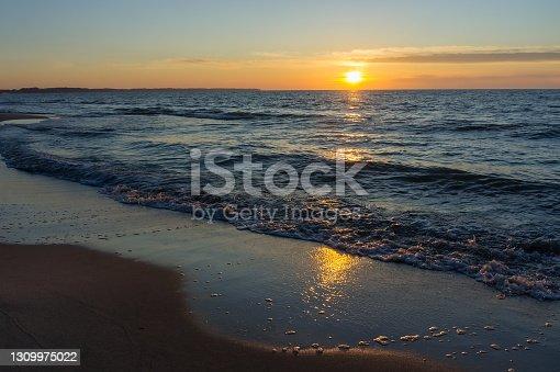 istock sunset on the sea coast, sunrise on the sea, the sun sets over the horizon on the sea 1309975022