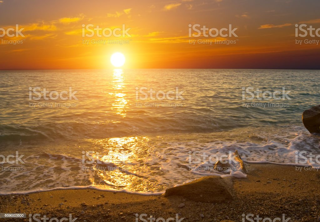 Sunset on the shore of sea royalty-free stock photo