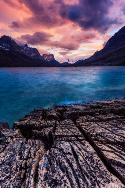 sunset on the shore of st mary lake in glacier national park, mo - st. mary lake stock pictures, royalty-free photos & images