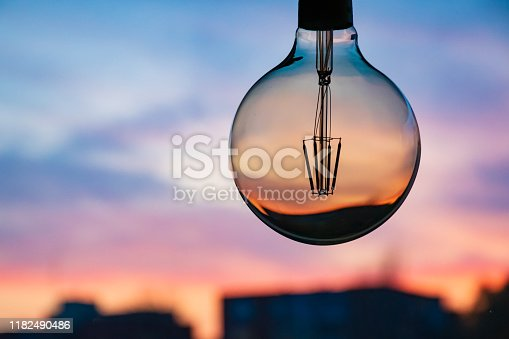 Beautiful defocused sunset in a light bulb. Sunset or sunrise background. Electricity concept. Earth hour. Energy consumption and environmental conservation, energy saving, city in the background