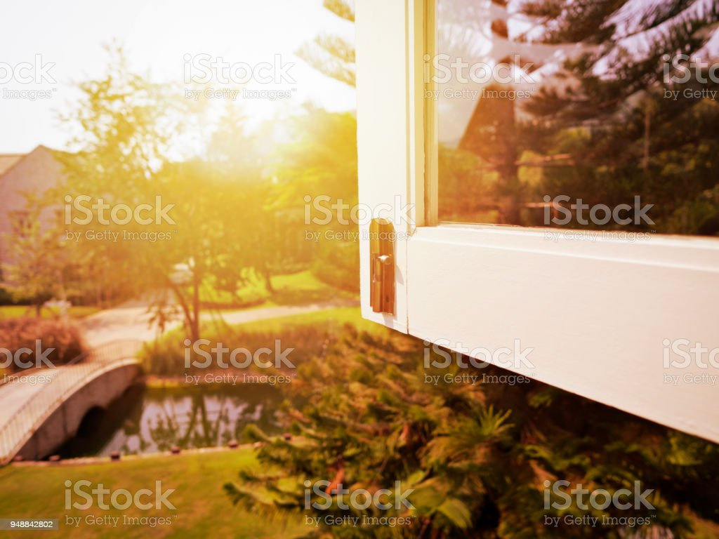 Sunset or sunrise view from window in bedroom, beautiful sun flare with pine trees garden and forest in a summer or winter season, vacation, weekend goals stock photo