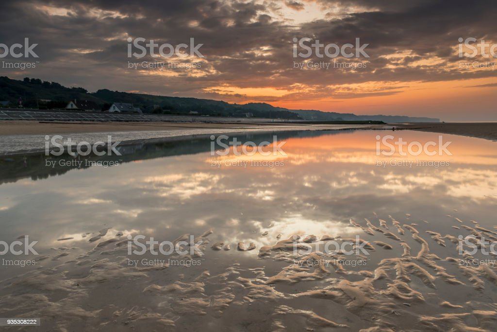 Sunset over a beach in Northern France. The sun is reflected in a shallow patch of sea water left behind by the retreating sea stock photo