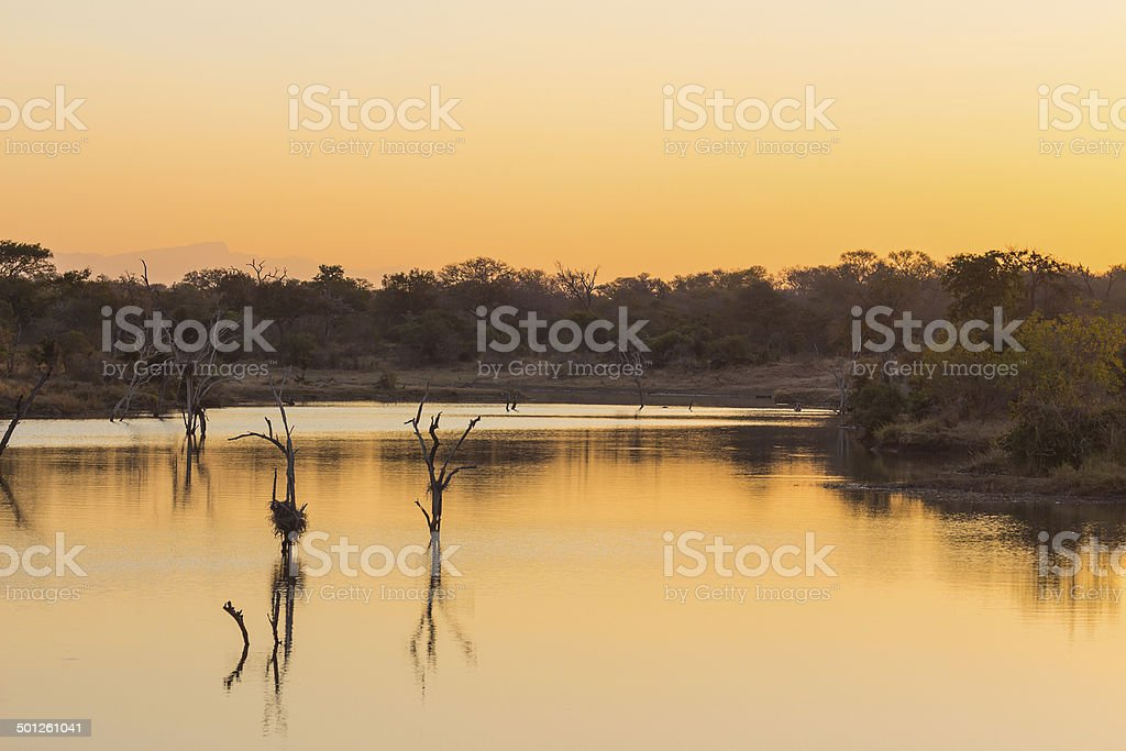 Sunset over a dam in the wild stock photo