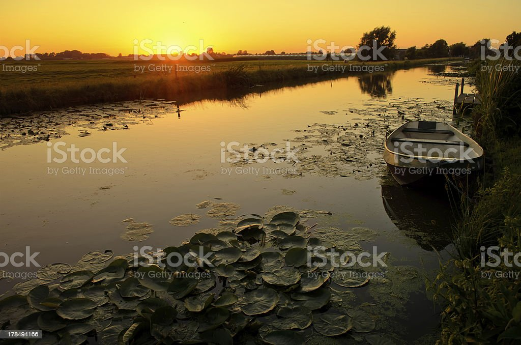 Sunset over a ditch with boat and waterlily stock photo