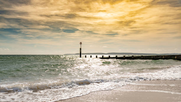 Sunset over a groyne on the beach stock photo