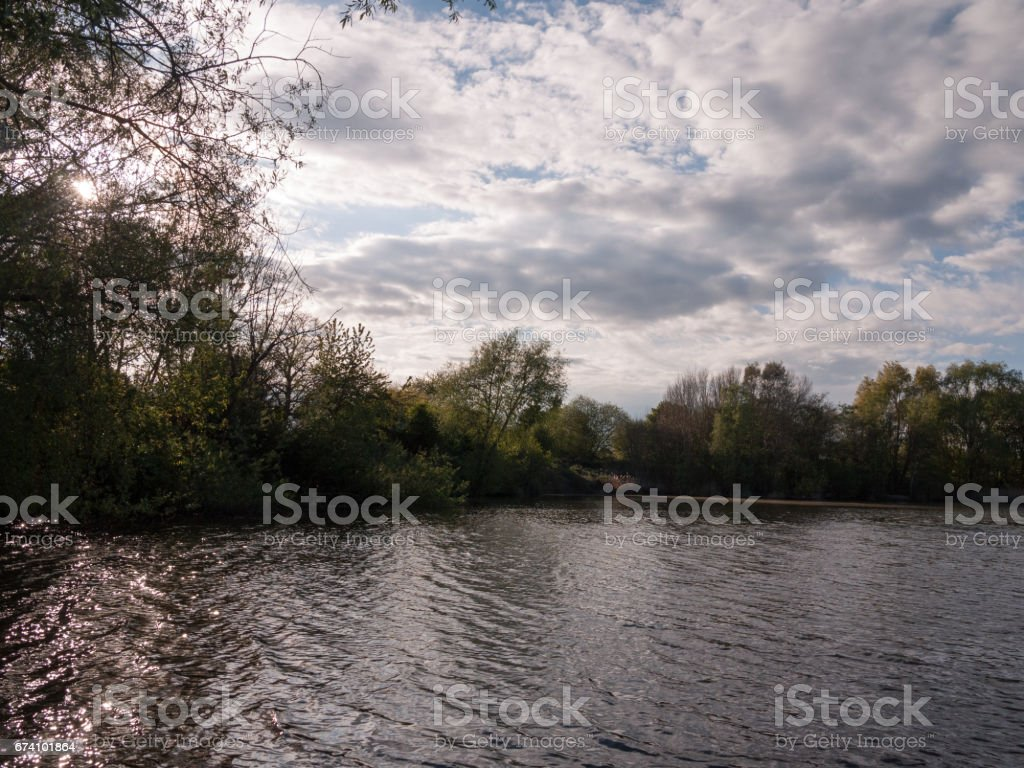 sunset over a lake in spring with moving waves ripples and clouds with trees around water royalty-free stock photo