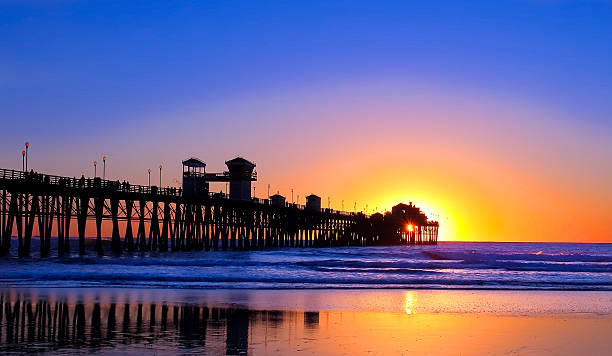 Sunset over a pier in California stock photo