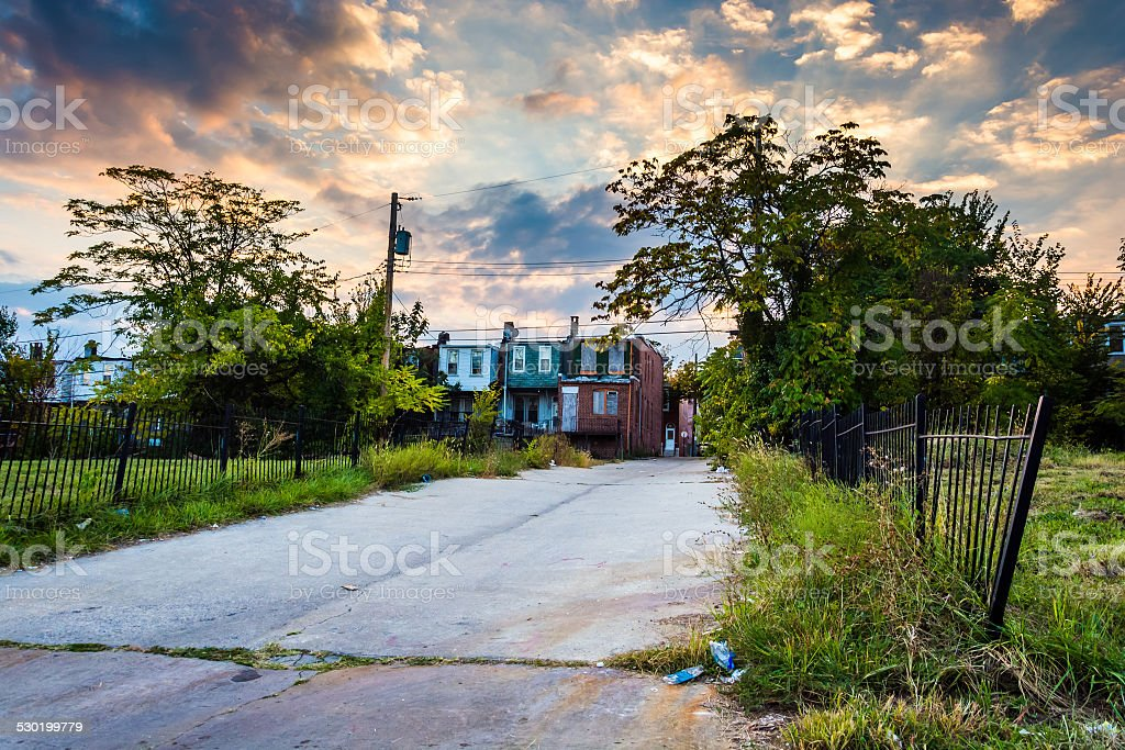 Sunset over a street and abandoned rowhouses in Baltimore, Maryl stock photo