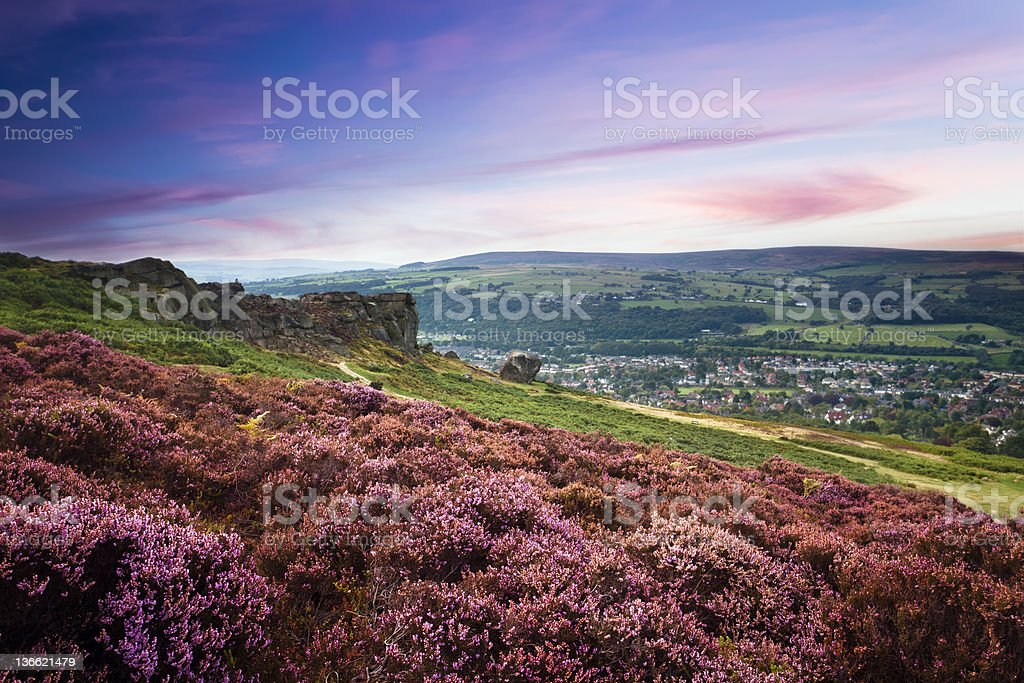 Sunset over a village and a hill of purple heather stock photo