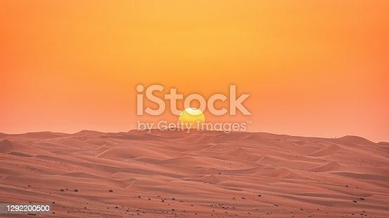 Sunset over the Abu Dhabi Empty Quarter Desert Sand Dunes. Desert Panorama of Empty Sea of Sand in the Rub' al Khali Desert under colorful orange sunset skyscape. Desert Sand Dunes close to Saudi Arabia and the United Arab Emirates. Abu Dhabi, United Arab Emirates, Middle East, Persian Gulf Countries