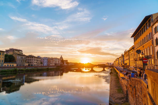 Sunset over Arno river in Florence, Italy. Spectacular sky, medieval bridge and buildings. stock photo