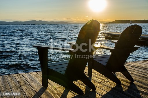 Sunset over Champlain lake with mountains in background and adirondack chair in foreground
