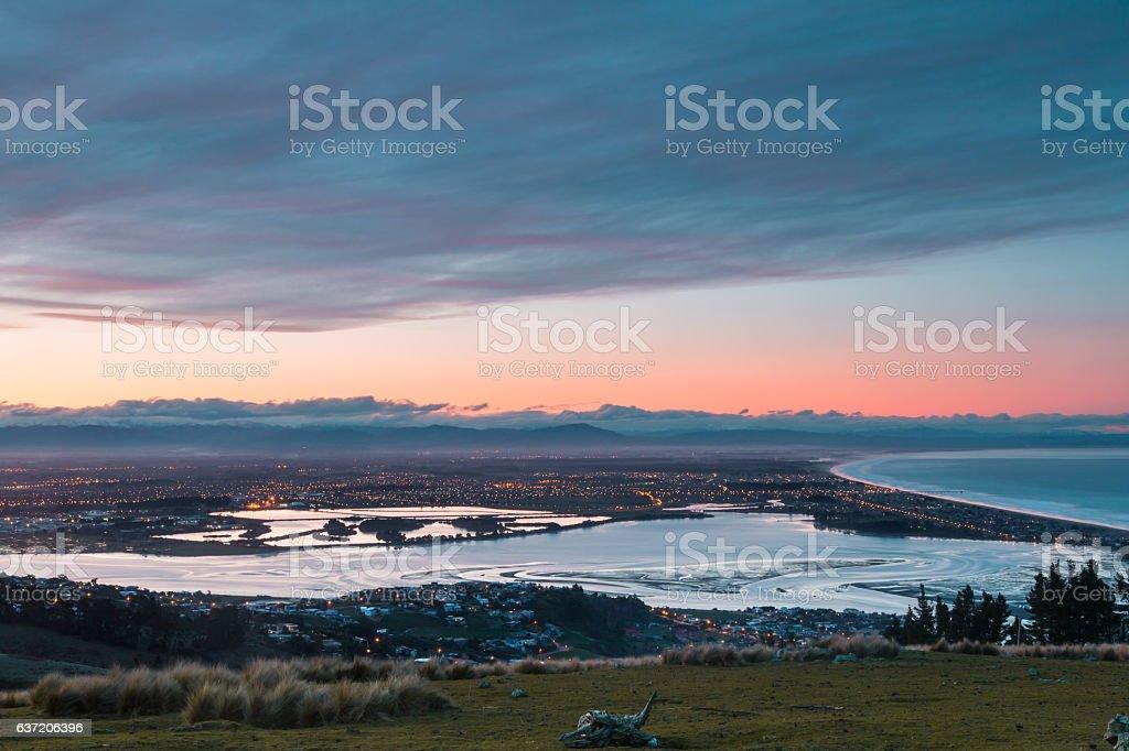 Sunset over city on ocean shore stock photo
