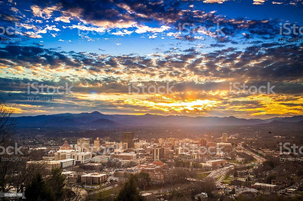 Sunset over Downtown Asheville North Carolina NC Epic Sunset over Downtown Asheville North Carolina NC cityscape with blue ridge mountain range and Mt. Pisgah featured in the background. Asheville Stock Photo
