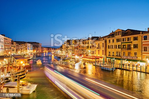 Venice, Italy - May 31, 2019: a lively evening with gondolas and small tourist vessels on Canal Grande. On Riva del Ferro and Riva del Vin, tourists enjoy a walking and refresh at local bars.