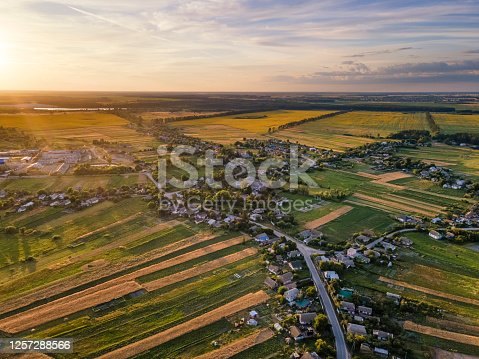 istock Sunset over green and yellow fields and small villages. 1257288566