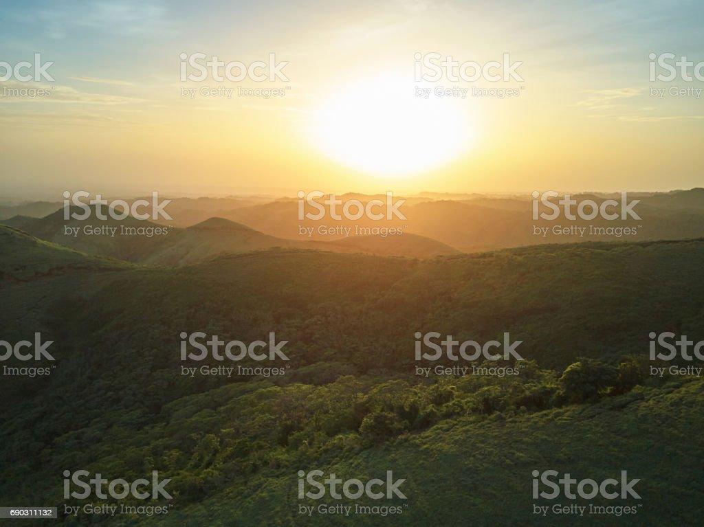 Sunset over green hills landscape stock photo