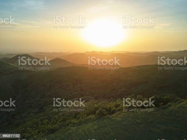 Photo of Sunset over green hills landscape