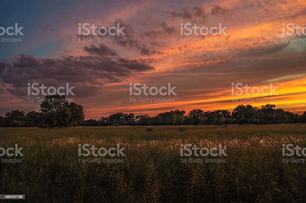 Sunset over hay bales and field in Sunnyvale, Texas royalty-free stock photo