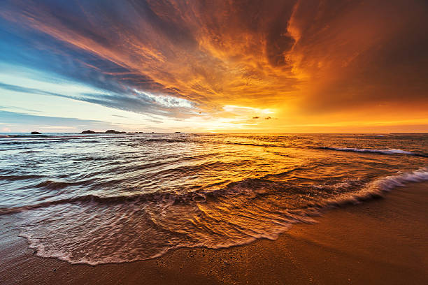sunset over indian ocean - dramatic sky stock photos and pictures