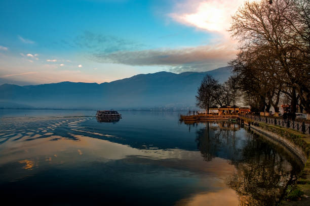 Sunset over Ioannina city and lake Pamvotis. seafront street for cars,pedestrians and bicycles .Epirus, Greece. stock photo
