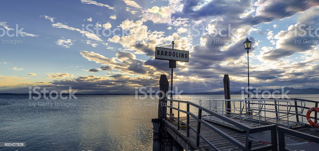 Sunset over lake Garda and pier in Bardolino Harbour Italy stock photo