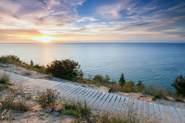 sunset over lake michigan and sleeping bear dunes - lake michigan stock pictures, royalty-free photos & images