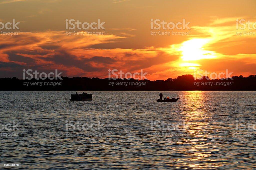 Sunset over Lake Washington with Pontoon and Fishing Boat stock photo