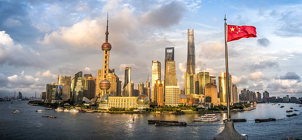 Sunset over Lujiazui Shanghai, China - July 7, 2016: Lujiazui financial district of Shanghai. Amazing sunset over the city with chinese flag in the picture. River Huangpu huangpu district stock pictures, royalty-free photos & images