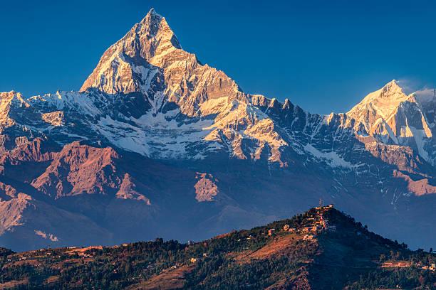 sonnenuntergang über machapuchare aus pokhara, nepal - nepal tibet stock-fotos und bilder
