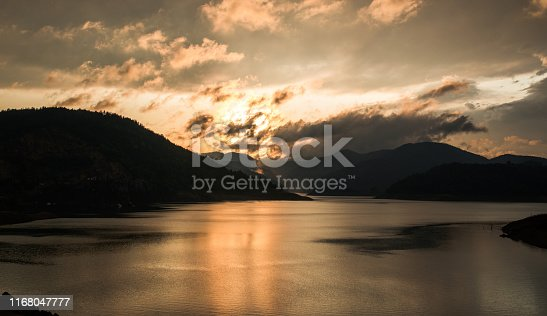 Beautiful sunset and dramatic cloudscape over mountain lake