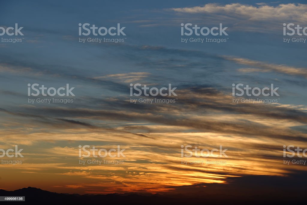 Sunset over mountain range on horizon with repeating clouds (wide) stock photo