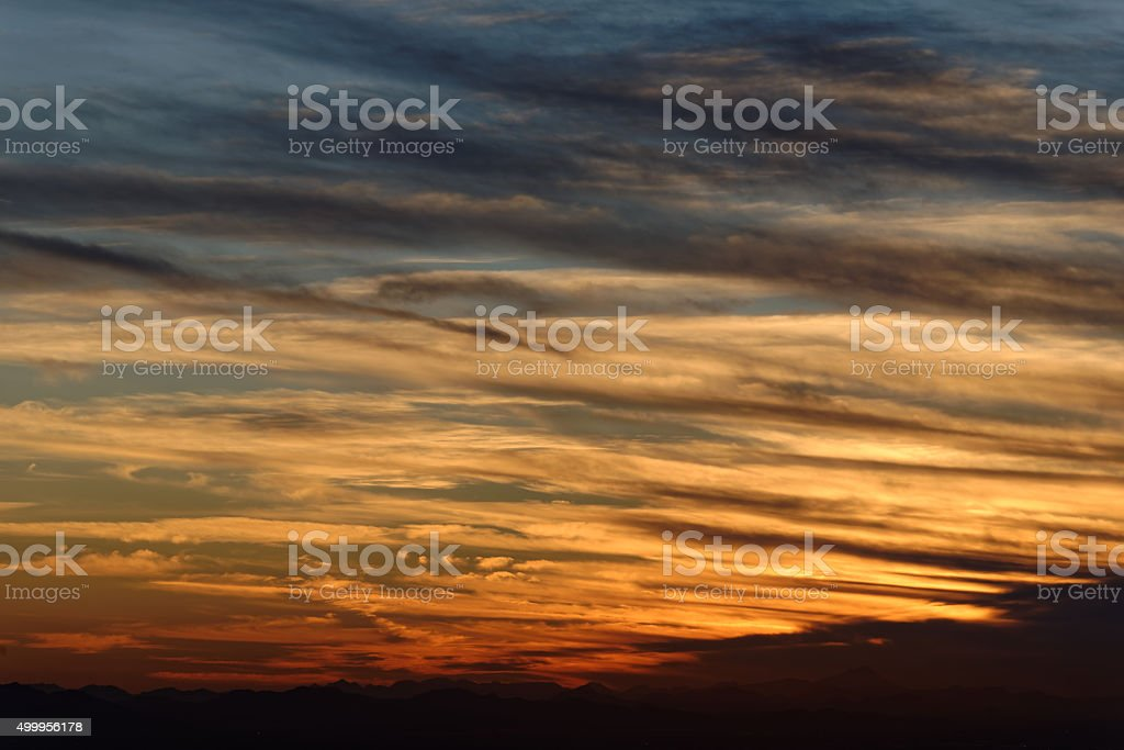 Sunset over mountain range on horizon with repeating clouds (normal) stock photo