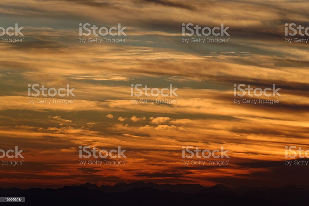 Sunset over mountain range on horizon with repeating clouds (tele) stock photo