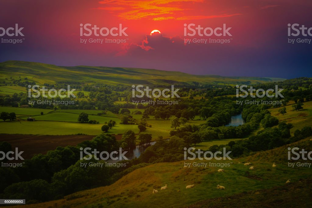 Sunset over mountains and meandering River making its way through lush green rural farmland in England. stock photo