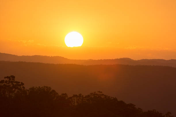 sunset over mountains - heat haze stock pictures, royalty-free photos & images