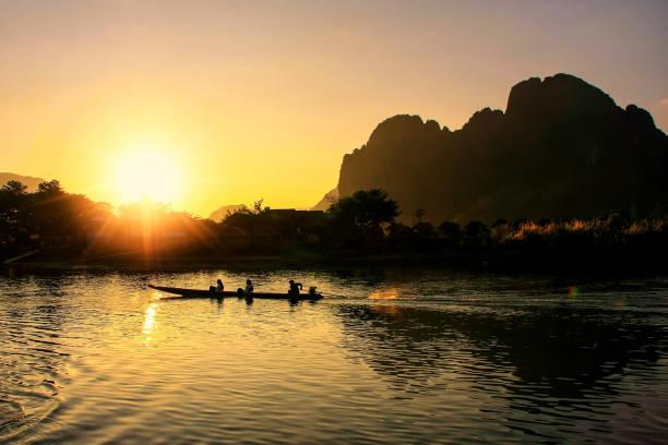 sonnenuntergang über nam song river in vang vieng, laos - vang vieng stock-fotos und bilder