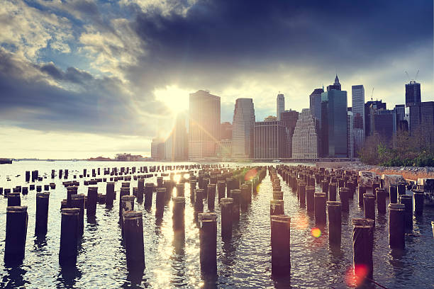 Sunset over New York City Row of groyns in front of Manhattan building during sunset.  south street seaport stock pictures, royalty-free photos & images