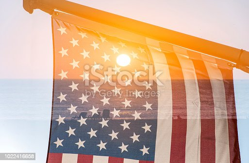 istock Sunset over Ocean and USA Flag as Background 1022416658