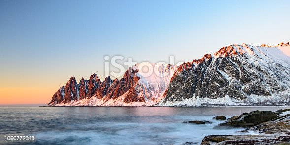 Sunset over the Okshornan mountain range at the island of Senja in Northern Norway at the end of a beautiful day in winter.